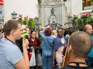Tourists and a guide visiting Manneken Pis in Brussels city center